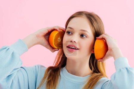 Photo pour Sourire jolie adolescente retenant des moitiés oranges près des oreilles d'isolement sur le rose - image libre de droit