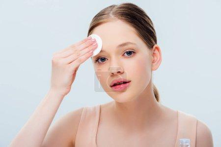 Photo pour Beau visage nettoyant d'adolescent avec le tampon de coton d'isolement sur le gris - image libre de droit