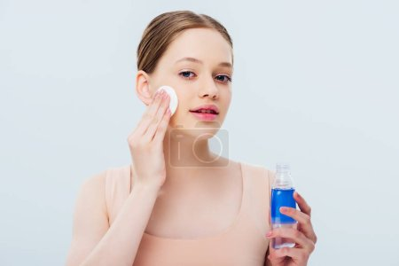 Photo for Pretty teenage girl applying lotion on face with cotton pad isolated on grey - Royalty Free Image
