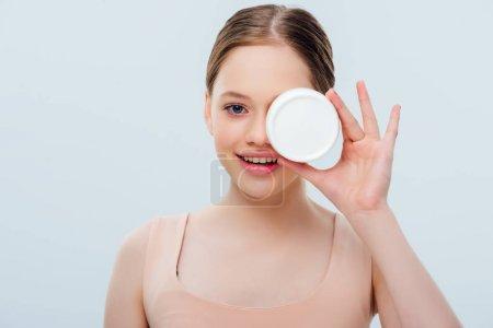 Photo pour Adolescente heureuse avec le visage obscur retenant la crème cosmétique d'isolement sur le gris - image libre de droit