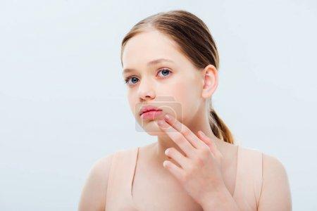 Photo pour Adolescente rêveuse touchant le visage et regardant loin isolé sur le gris - image libre de droit