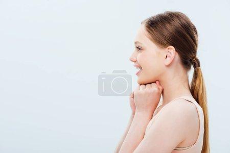 Photo pour Vue latérale de heureuse adolescente isolée sur gris - image libre de droit