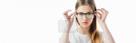 Photo for Panoramic shot of serious teenage girl touching glasses and looking at camera isolated on white - Royalty Free Image