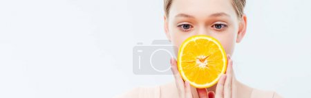 Photo for Teenage girl with obscure face holding ripe orange half isolated on white, panoramic shot - Royalty Free Image