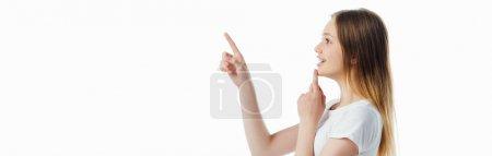 Photo pour Vue latérale d'une adolescente joyeuse pointant du doigt isolé sur blanc, plan panoramique - image libre de droit