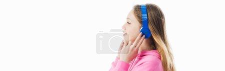 Photo pour Vue de côté de l'adolescente touchant des écouteurs sur la tête d'isolement sur le blanc, projectile panoramique - image libre de droit
