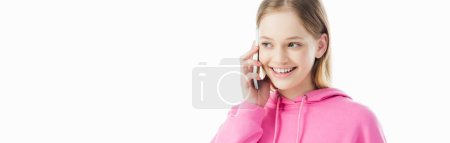Photo for Panoramic shot of happy teenage girl in pink hoodie talking on smartphone isolated on white - Royalty Free Image