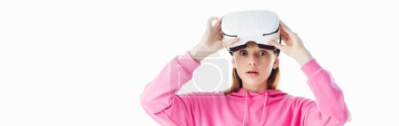 Photo for Panoramic shot of shocked teenage girl in pink hoodie wearing vr headset isolated on white - Royalty Free Image