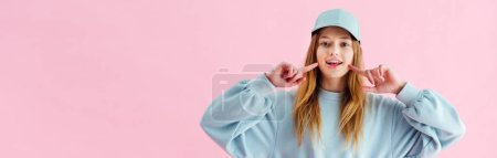 Photo for Panoramic shot of pretty teenage girl in cap pointing with fingers at smile isolated on pink - Royalty Free Image