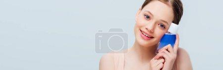Photo pour Adolescente gaie retenant la lotion bleue d'isolement sur le gris, projectile panoramique - image libre de droit