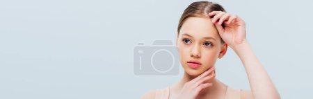 Photo pour Adolescente réfléchie touchant le visage d'isolement sur le gris, projectile panoramique - image libre de droit