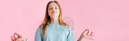 Photo pour Tir panoramique de jolie adolescente avec les yeux fermés méditant isolé sur le rose - image libre de droit