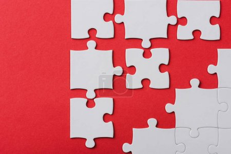 top view of unfinished jigsaw puzzle pieces isolated on red