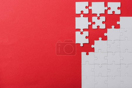 Photo for Top view of unfinished and white jigsaw puzzle pieces isolated on red - Royalty Free Image