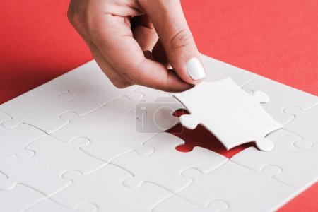 cropped view of woman holding white jigsaw near connected puzzle pieces on red