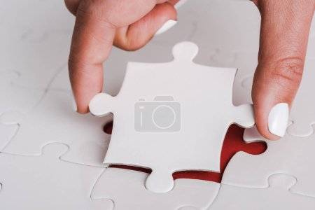 close up of woman holding white jigsaw near connected puzzle pieces