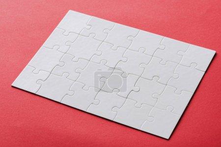 Foto de White connected jigsaw connected puzzle pieces on red - Imagen libre de derechos