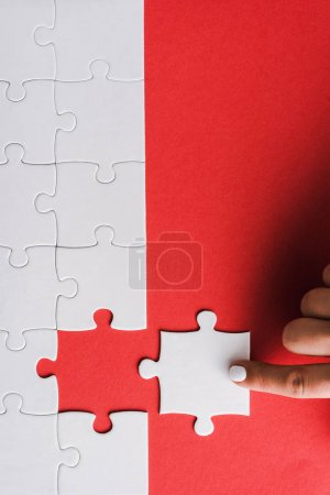 Photo for Top view of woman pointing with finger at white jigsaw near connected puzzle pieces on red - Royalty Free Image