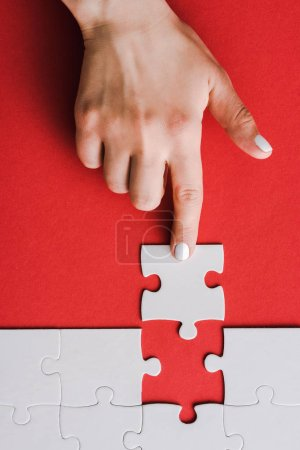 top view of woman pointing with finger at jigsaw near connected white puzzle pieces on red