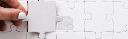 Photo for Panoramic shot of woman holding white jigsaw near connected puzzle pieces - Royalty Free Image