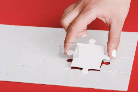 cropped of woman holding jigsaw near connected white puzzle pieces on red