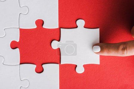 Ausgeschnittene Ansicht einer Frau, die mit dem Finger auf Puzzleteile in der Nähe von miteinander verbundenen weißen Puzzleteilen auf Rot zeigt