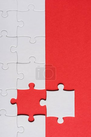 Photo for Top view of incomplete jigsaw near white puzzle piece isolated on red - Royalty Free Image