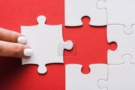Photo for Cropped of woman touching jigsaw near connected white puzzle pieces on red - Royalty Free Image