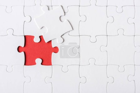 Photo pour Top view of white incomplete jigsaw near puzzle piece - image libre de droit