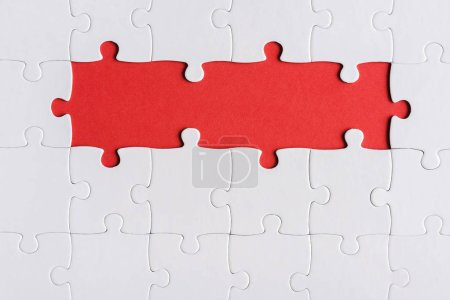 Photo pour Top view of connected jigsaw puzzle pieces isolated on red - image libre de droit