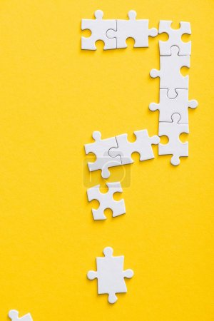 Photo for Top view of connected white jigsaw puzzle pieces isolated on yellow - Royalty Free Image