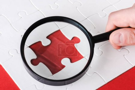 Photo for Cropped view of man holding magnifying glass near jigsaw shape on red - Royalty Free Image
