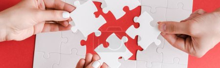 Photo for Panoramic shot of man and woman holding white puzzle pieces on white - Royalty Free Image