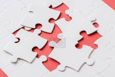 unfertige Puzzleteile in der Nähe miteinander verbundener weißer Puzzleteile auf rot
