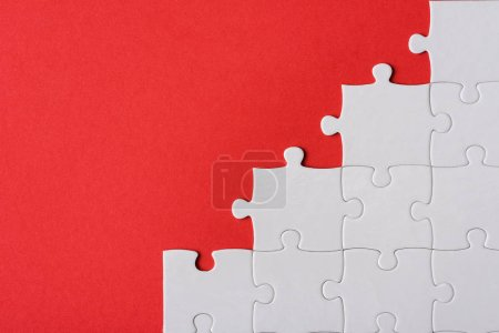 Photo for Top view of connected white puzzle pieces isolated on red - Royalty Free Image