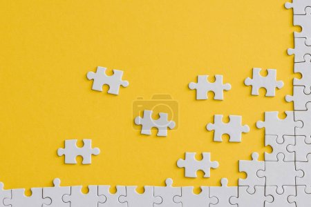 Photo for Top view of unfinished jigsaw near connected white puzzle pieces isolated on yellow - Royalty Free Image