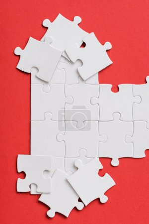 Photo for Top view of white unfinished jigsaw near connected puzzle pieces isolated on red - Royalty Free Image