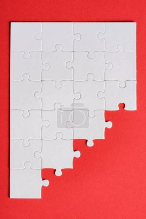 Photo for Top view of white connected puzzle pieces isolated on red - Royalty Free Image