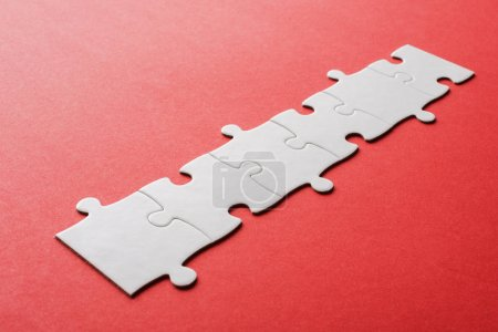 Photo for White line of connected jigsaw puzzle pieces on red - Royalty Free Image