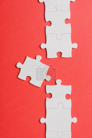 Photo for Top view of white connected jigsaw near puzzle piece isolated on red - Royalty Free Image