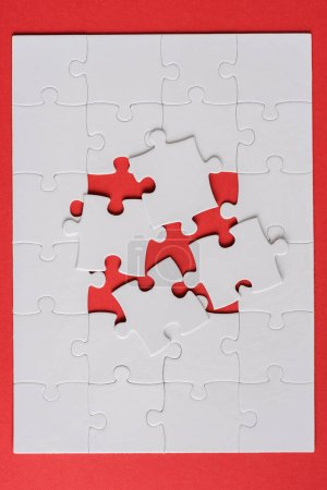 Photo for Top view of white jigsaw near connected puzzle pieces on red - Royalty Free Image