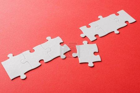 Photo pour White connected jigsaw near puzzle piece on red - image libre de droit