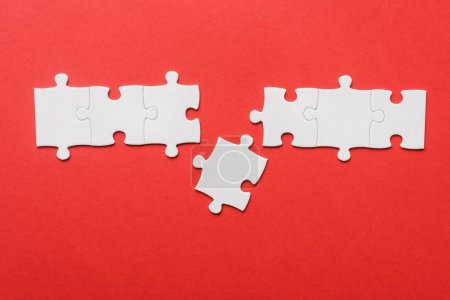 Photo for Top view of connected jigsaw near puzzle piece on red - Royalty Free Image