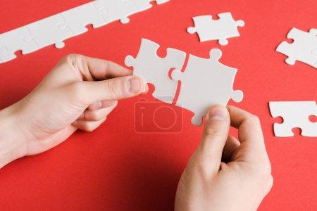 abgeschnittene Ansicht eines Mannes, der weiße Puzzleteile in Händen auf Rot verbindet