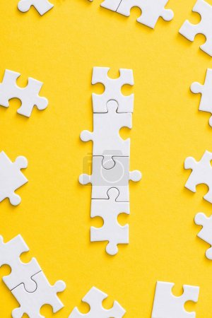 Photo for Top view of connected white puzzle pieces isolated on yellow - Royalty Free Image