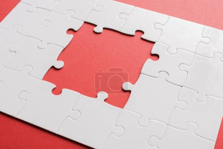 Photo for Unfinished and connected white jigsaw puzzles on red - Royalty Free Image