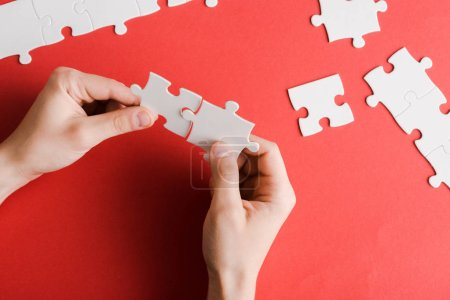 cropped view of man holding white puzzle pieces in hands on red