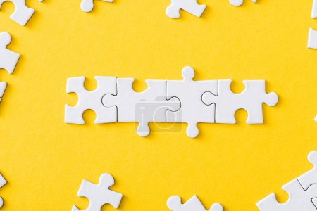 Photo for Top view of connected line with white jigsaw puzzles isolated on yellow - Royalty Free Image