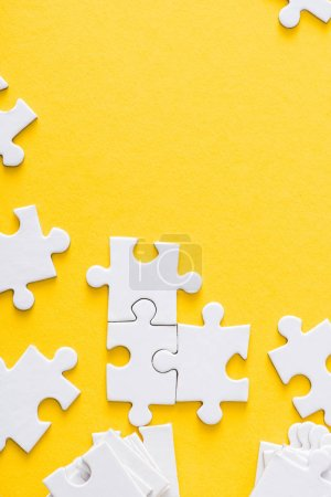 Photo pour Top view of white connected puzzles isolated on yellow - image libre de droit