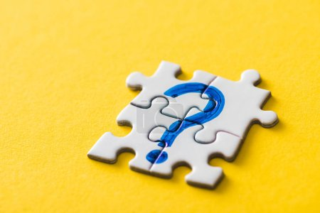 Photo for Connected jigsaw puzzle pieces with drawn blue question mark on yellow - Royalty Free Image